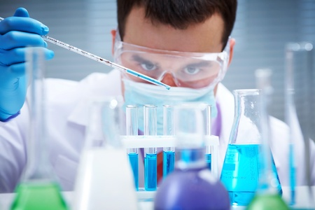 biochemist: Investigator checking test tubes. Man wears protective goggles