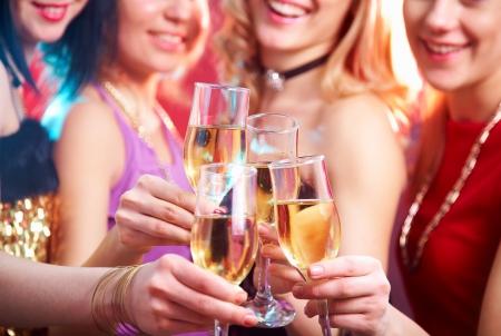 Mooie meisjes rinkelen glazen champagne op een feestje Stockfoto