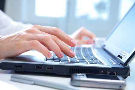 Human hands working on laptop on office background photo