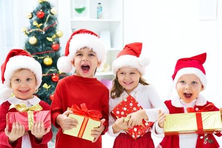 fiesta familiar: Grupo de los cuatro hijos en el sombrero de la Navidad con regalos