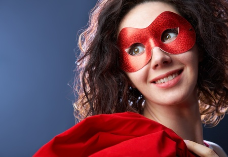 mystery woman: Portrait of playful beautiful young woman wearing red carnival mask Stock Photo