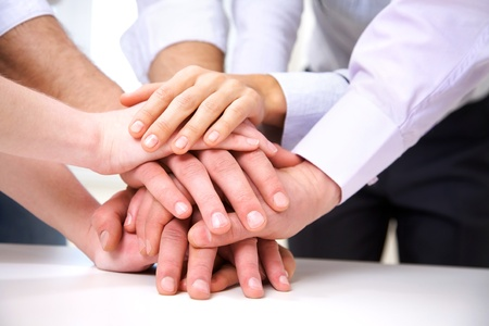 unanimous: diverse group of workers with their hands together in form of teamwork Stock Photo