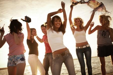 fiestas discoteca: grupo de j�venes felices bailando en la playa en la puesta de sol hermosa del verano Foto de archivo