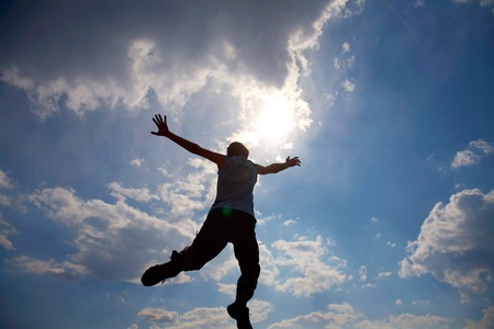 Young man is jumping against cloudy sky. Use it for lifestyle concepts photo