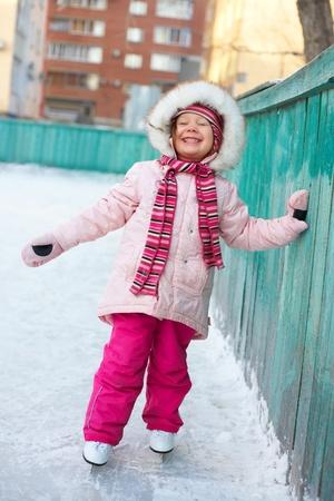 patinaje sobre hielo: Ni�a aprender a patinar en la pista cerca de la casa Foto de archivo