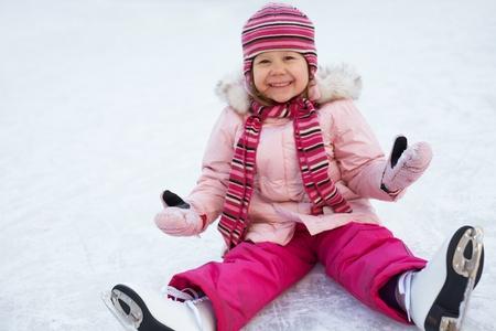 patinando: ni�a en una chaqueta de color rosa, sentada en el hielo con los patines en los pies despu�s de la ca�da Foto de archivo
