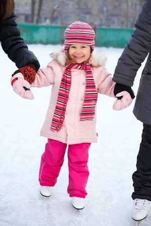 ice skating: little girl learns to skate in the yard with older girlfriends Stock Photo
