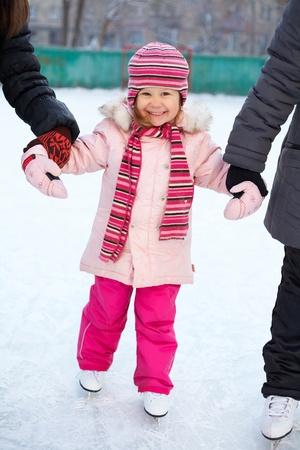 patinaje sobre hielo: ni�a aprende a patinar en el patio con mayores novias