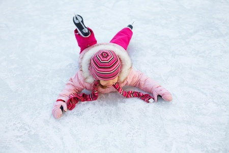 contusion: little girl in a pink jacket fell to the ice while skating