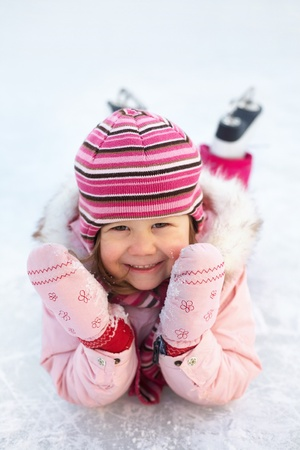little girl in skates on the ice rink lies and laughs photo