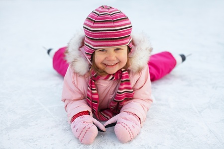 skating rink: little girl in skates on the ice rink lies and laughs Stock Photo