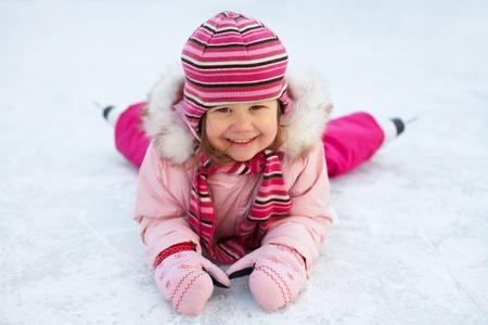 patinaje sobre hielo: niña en patines en la pista de hielo se encuentra y se ríe Foto de archivo