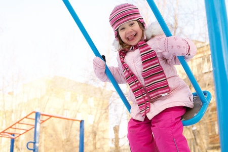 little girl riding her backyard swing in the winter photo