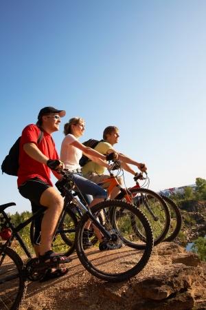 Drie vrienden op de fiets op de rand van een rots en kijken verre van rock breuk