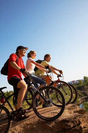 Touring: Trzej przyjaciele na rowerach na krawÄ™dzi skaÅ'y i wyglÄ…dajÄ… z daleka od stÅ'uczenia rocka Zdjęcie Seryjne