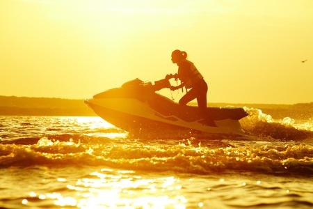 schönes Mädchen Reiten ihr Jetskis in das Meer bei Sonnenuntergang. Spray