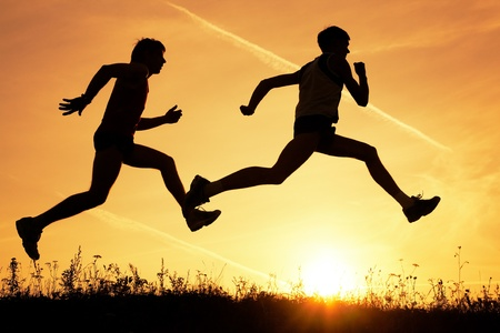 Two men make jog in the field on a sky background by at sunset photo