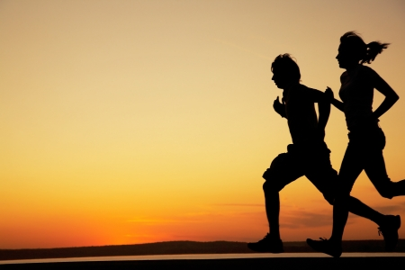 gente corriendo: Pareja joven: el hombre y la mujer de forma conjunta en una puesta de sol en la costa del lago. Silueta.