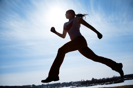 healthy exercise: Female runner silhouette against the blue sky and sun Stock Photo