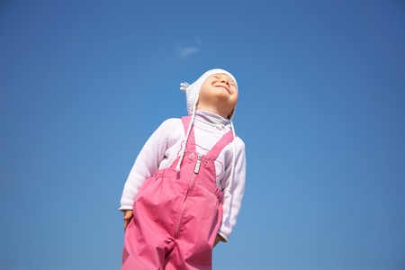 Little cute girl in white cap enjoying on blue sky background  photo