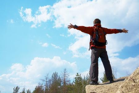 osiągnął: Szczęśliwy turysta mężczyzna trzyma rÄ™ce w powietrzu w poczuciu sukcesu, którzy osiÄ…gnÄ™li szczyt