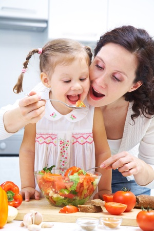 Mother and daughter eating vegetables salad in kitchen photo