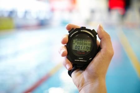 sled: hand of coach with a stopwatch during competitions in the swimming pool