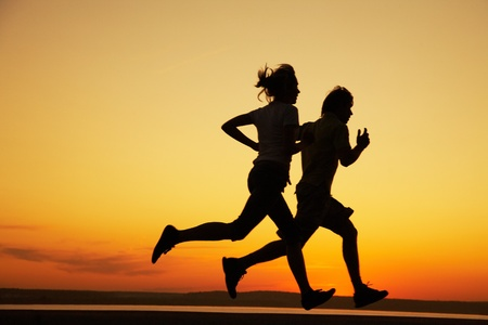 Young couple: man and woman run together on a sunset on lake coast. Silhouette photo