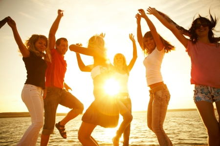 group of happy young people dancing at the beach on beautiful summer sunset photo