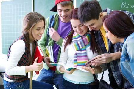 youth group: Group of students discussing in classroom Stock Photo