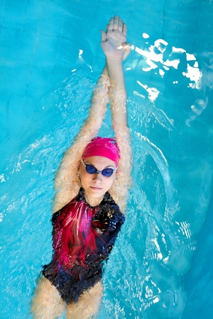 swim race: young woman swims on back in the pool