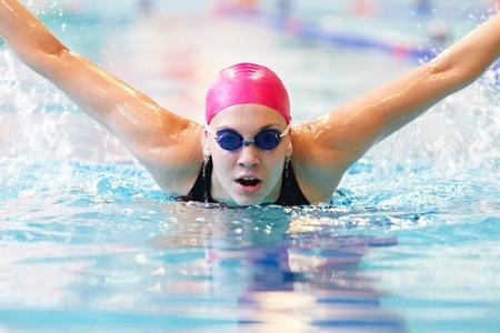 natacion: mujer joven nada la mariposa en la piscina Foto de archivo