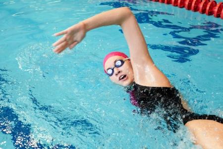 jong meisje zwemt vrije slag in het zwembad Stockfoto