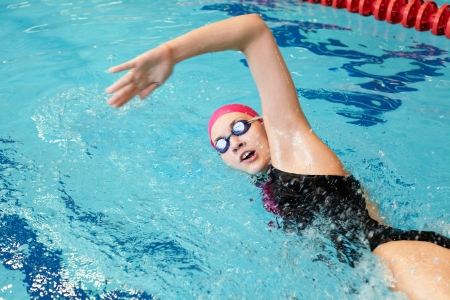swimming race: young girl swims freestyle in the pool