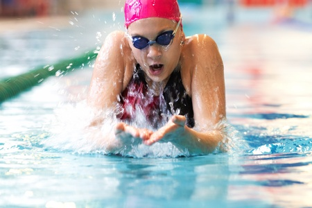 swimming competition: young girl swims breaststroke in the pool