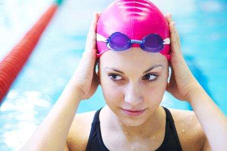 Retrato de una hermosa chica con una gorra roja en la piscina