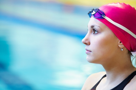 Portrait of a beautiful girl in a red cap at the pool