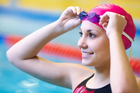 competitive: young woman wears glasses in front of the swimming pool. Back.