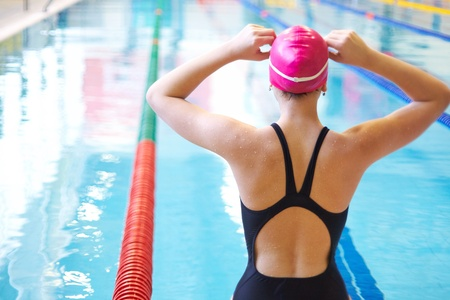young woman wears glasses in front of the swimming pool. Back. Imagens