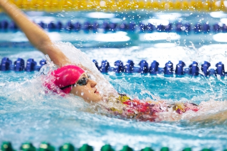 swim race: Young girl floating on her back in the pool Stock Photo