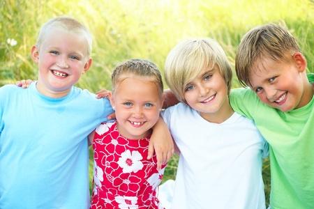ni�os contentos: felices los ni�os al aire libre mirando a la c�mara durante el verano