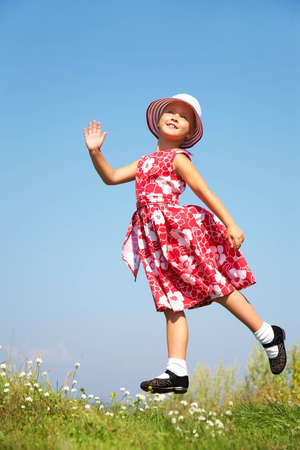 Cute girl jumping on summer meadow against blue sky photo