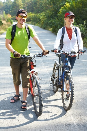 Couple  bicycler  walking with bikes from park photo
