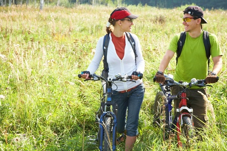 Couple of cyclists riding bicycles in meadow Stock Photo - 12508080