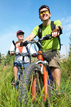 recreational vehicle: Couple of cyclists riding bicycles in meadow Stock Photo