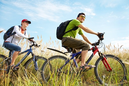 countryside: Couple of cyclists riding bicycles in meadow Stock Photo