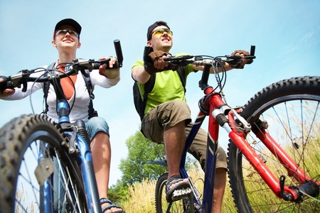 relaxation exercise: Couple of cyclists riding bicycles in meadow Stock Photo