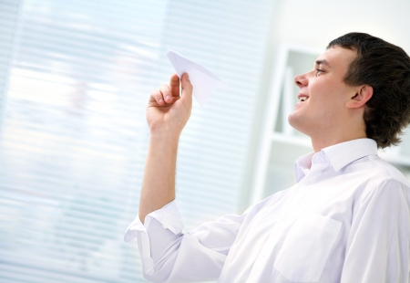 only young adults: young businessman starts  paper airplane in the office Stock Photo