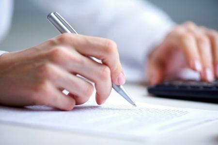 Foto von H�nden halten Stift unter der Dokumentennummer und Dr�cken Taschenrechner-Tasten