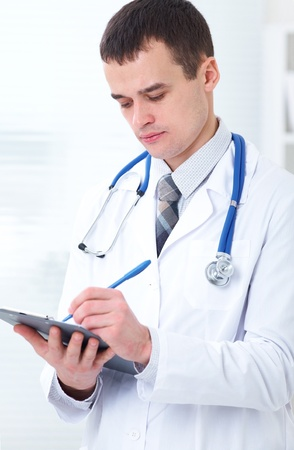 young male doctor makes an entry in the tablet at work photo